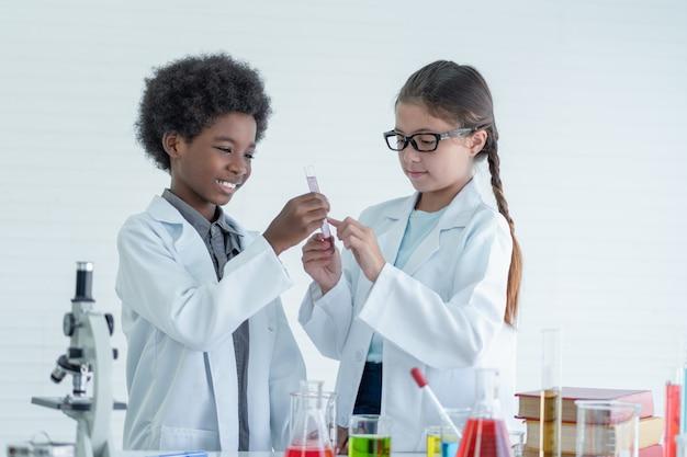 Due scienziati dei bambini che fanno esperimenti chimici con il microscopio alla ricerca nella stanza del laboratorio.
