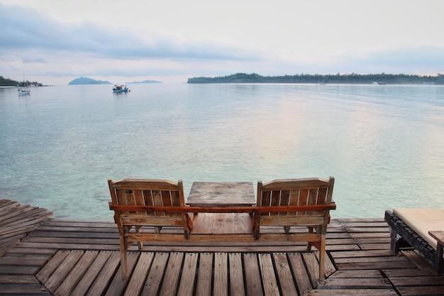 Due sedia in legno sul pavimento di legno con sfondo blu del mare