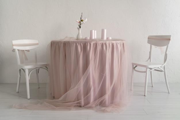 Due sedie bianche e tavolo coperto con tovaglie rosa