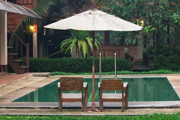Due sedie di legno si trovano accanto alla piscina