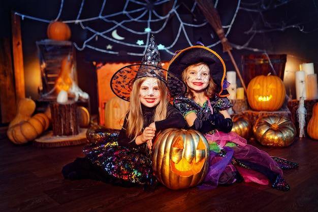 Due simpatiche sorelle divertenti celebrano la festa. bambini allegri in costumi di carnevale pronti per halloween.