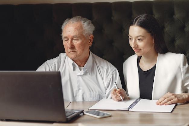 Due soci d'affari che lavorano con un computer portatile in un caffè