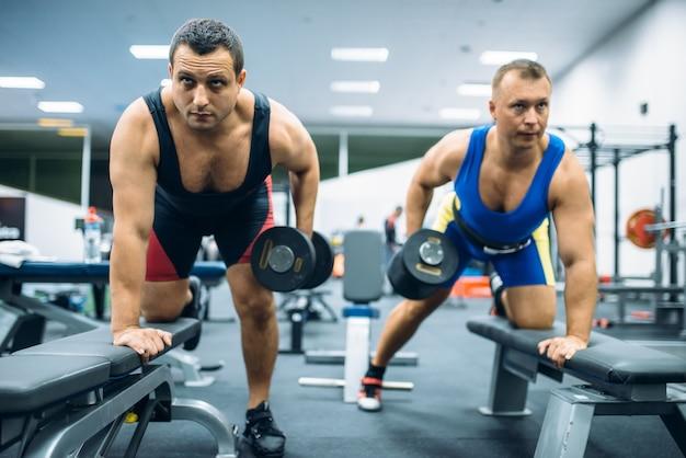 Due sollevatori di pesi maschi che fanno esercizio sulla panchina con manubri