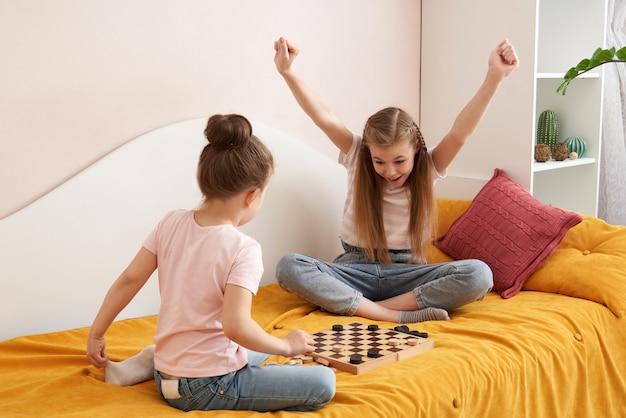 Due sorelle che giocano a dama su un cattivo divertimento a casa, concetto di bambini felici