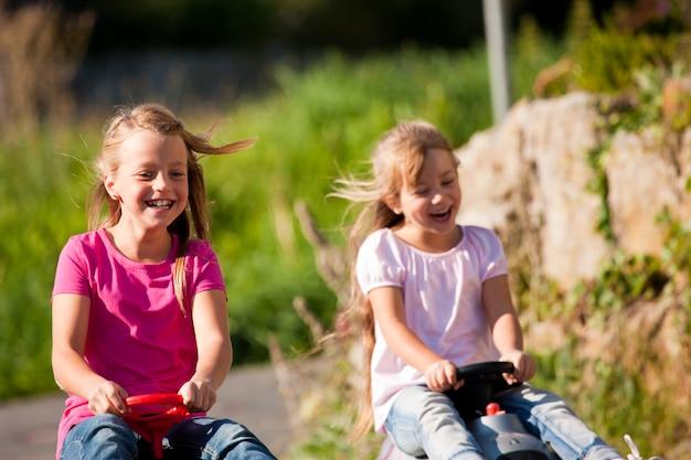 Due sorelle con le macchinine che li guidano giù per una collina con incredibili quantità di divertimento