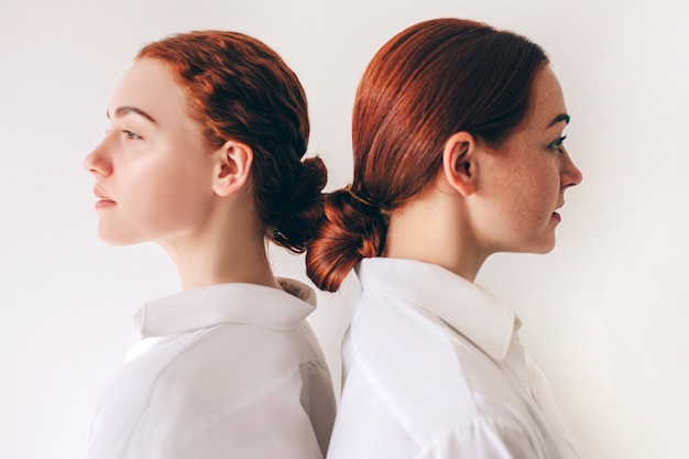 Due sorelle dai capelli rossi stanno isolato su uno sfondo bianco in camicie. donne in piedi con le spalle l'una all'altra. i capelli sono attorcigliati in un fascio. hanno i capelli lisci e i riccioli.