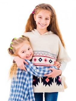 Due sorelle delle bambine nell'abbracciare dell'abbigliamento casual