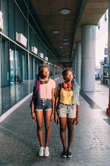Due sorelle delle donne che propongono città all'aperto che osserva via