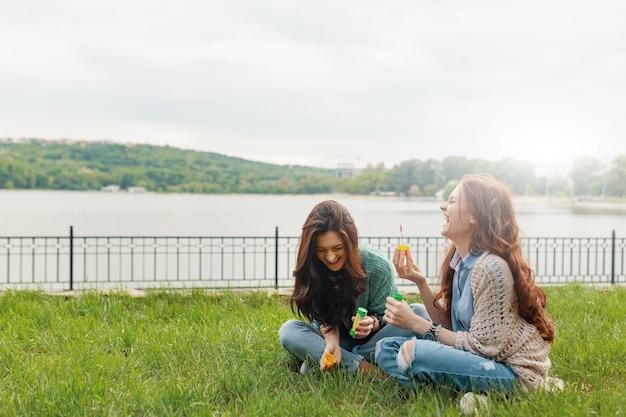 Due sorelle divertendosi mentre fanno le bolle e sedendosi sul g