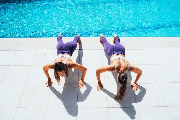 Due sorelle gemellate femminili che fanno esercizio relativo alla ginnastica accanto allo stagno