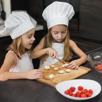 Due sorelle in cappello del cuoco unico e grembiule che tagliano uova sode sul tagliere di legno