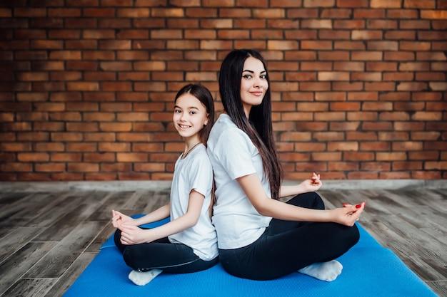Due sorelle in forma seduti schiena contro schiena in palestra e praticare yoga.