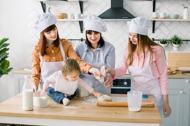 Due sorelle, la nonna e la piccola figlia cucinano la torta di vacanza in cucina per la festa della mamma, serie di foto di lifestyle casual nella vita reale degli interni