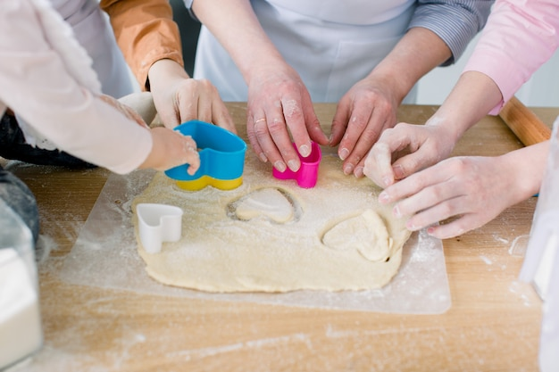 Due sorelle, la nonna e la piccola figlia del bambino stanno cucinando nella cucina al giorno di madri, serie di foto di stile di vita nell'interno domestico luminoso. mani che tagliano i biscotti dei cuori dalla festa della mamma della pasta