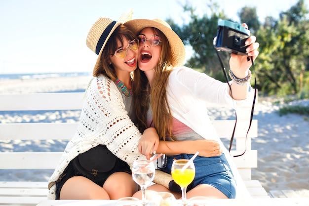 Due sorelle piuttosto divertenti che fanno selfie con la fotocamera vintage, in posa sulla spiaggia, atmosfera di festa e vacanza, sensazione pazza positiva, occhiali da sole e cappelli di vestiti luminosi estivi.