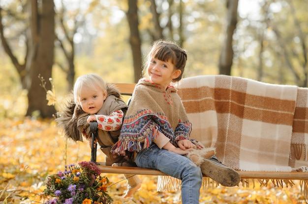 Due sorelle sono seduti su una panchina in un parco in autunno.