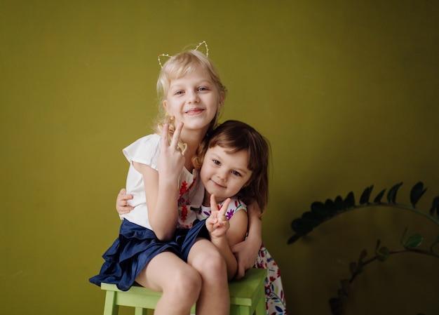 Due sorelline abbastanza giovani alla moda che posano allo studio