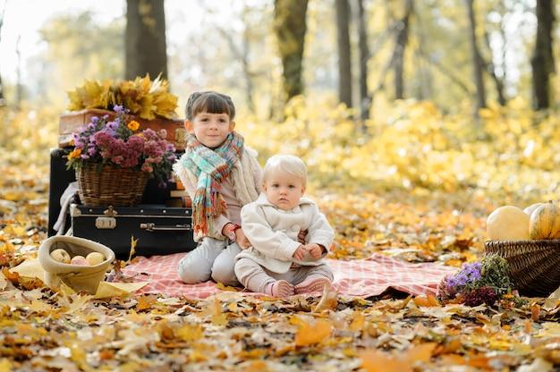 Due sorelline si abbracciano sulla spiaggia durante un picnic nel parco. tempo d'autunno.