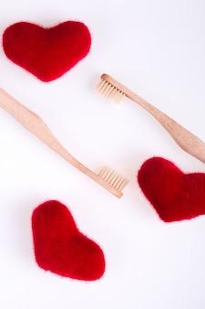 Due spazzole dentali beige con cuori rossi su sfondo bianco. isolato.