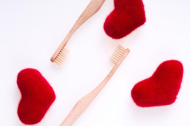 Due spazzole dentali beige con i cuori rossi su bianco. isolato. amore. san valentino.