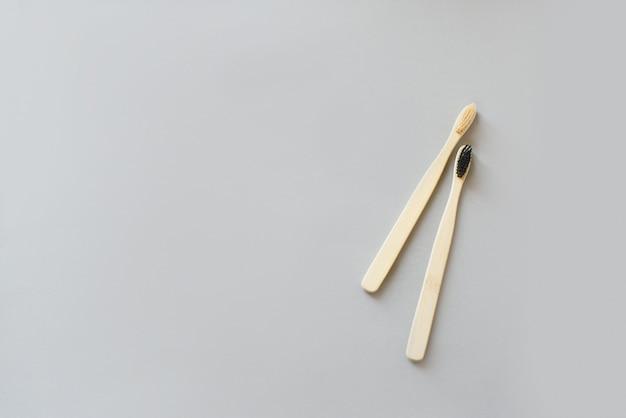 Due spazzole di bambù per lavarsi i denti su uno sfondo grigio. posto per il testo, vista dall'alto.