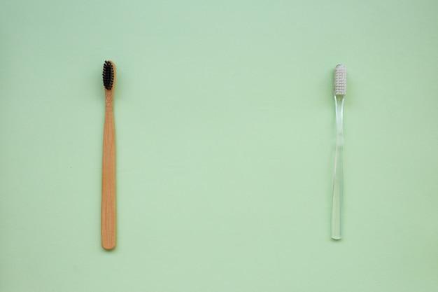 Due spazzolini da denti: bambù naturale e plastica su uno sfondo di carta verde