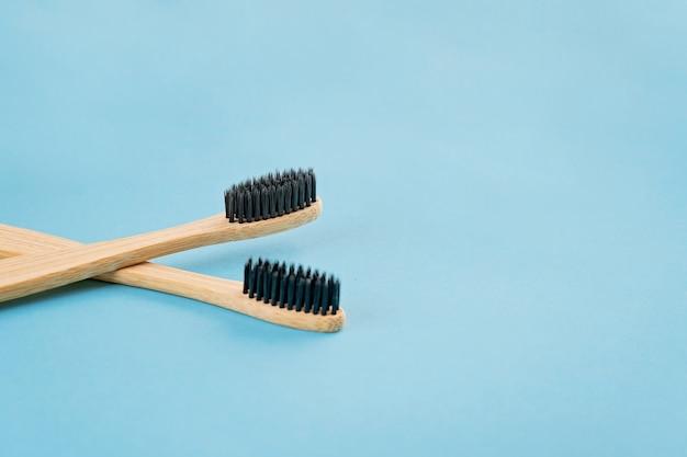 Due spazzolini da denti di bambù sulla superficie bluw. stile di vita ecologico
