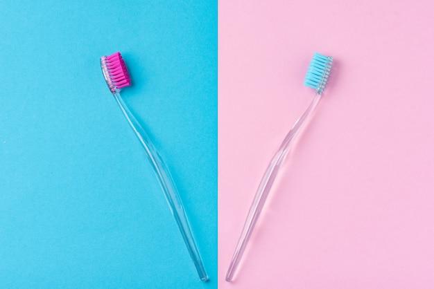 Due spazzolini da denti di plastica su un colorato blu e rosa, da vicino
