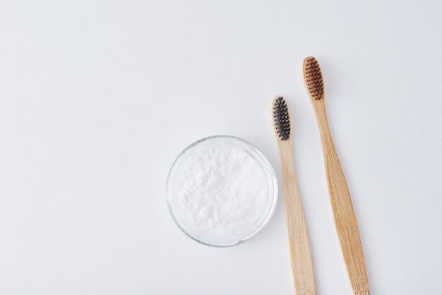 Due spazzolini da denti in legno di bambù e bicarbonato di sodio in barattolo di vetro su uno sfondo rosa. denti salute e mantenere il concetto di bocca