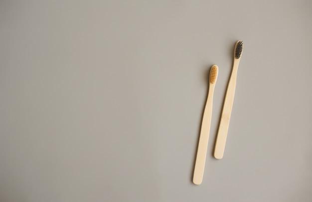 Due spazzolini da denti in legno, su uno sfondo grigio. proteggere la natura, dalla plastica.