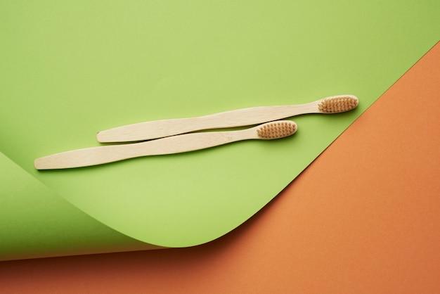 Due spazzolini da denti in legno su uno sfondo verde arancio,