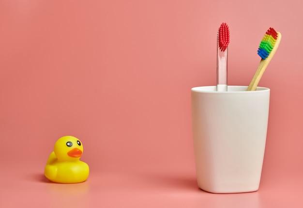 Due spazzolino da denti e giocattoli dell'anatra, copyspace. strumento per la cura personale per proteggere la cavità orale, rimuovere la placca e il tartaro.