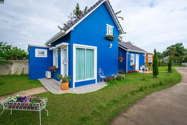 Due stili di casa blu decorati con giardino anteriore e vaso di fiori. stile casa, semplice de