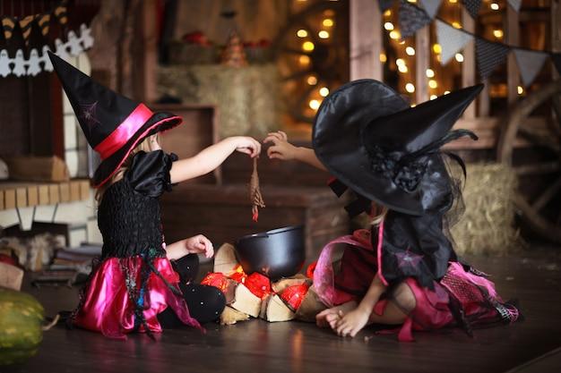 Due streghe in costume e cappelli evocano la pentola, infanzia di halloween,