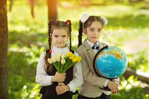 Due studentesse di ragazze caucasiche allegre con fiori e un globo