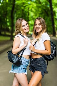 Due studenti felici che camminano e si parlano nel parco estivo