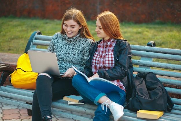 Due studenti seduti su una panchina con laptop e libro