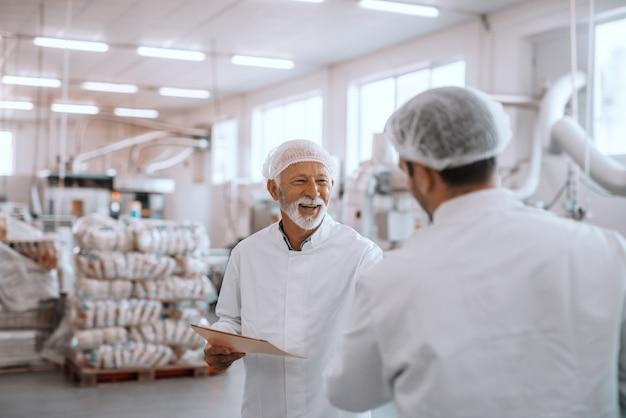 Due supervisori discutono sulla qualità del cibo nelle piante alimentari. uno più vecchio che tiene una cartella con i dati. entrambi indossano uniformi sterili bianche e hanno una retina per capelli.