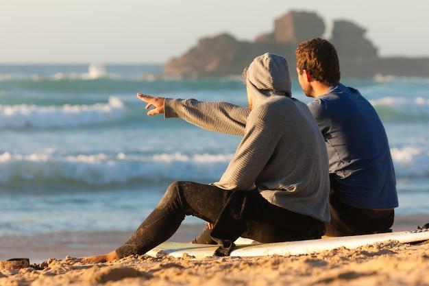 Due surfisti che parlano sulla spiaggia