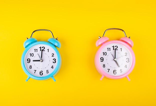 Due sveglie su uno sfondo giallo brillante che mostra tempi diversi come il concetto di inizio e fine della giornata lavorativa