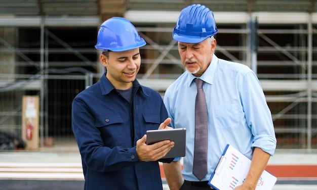 Due sviluppatori di architetti che esaminano i piani di costruzione in cantiere usando un tablet