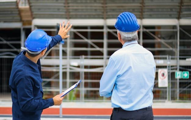 Due sviluppatori di architetti che esaminano i piani di costruzione in cantiere