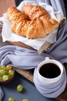 Due tazze bianche di cappucino e biscotti di farina d'avena sulla tavola di legno blu.