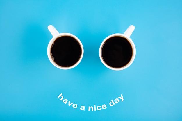 Due tazze da caffè bianche con un sorriso su sfondo blu con la frase buona giornata
