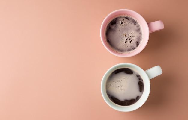 Due tazze di caffè con latte di colore rosa e menta su fondo marrone