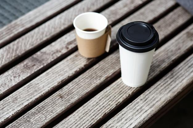Due tazze di caffè da portare in piedi sulla panca di legno