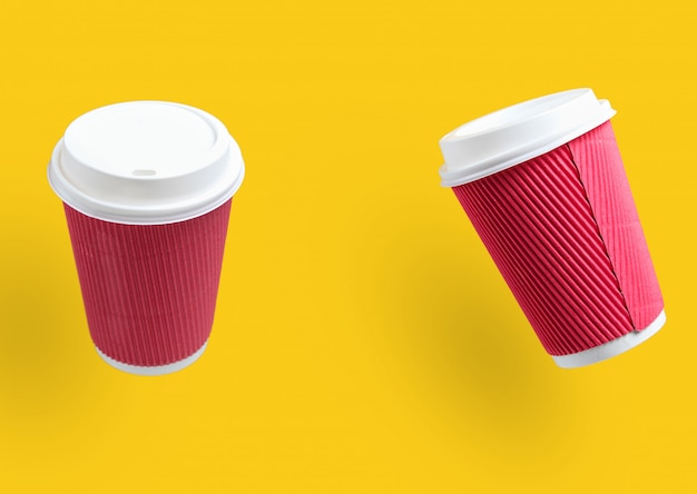Due tazze di caffè di carta gialle su giallo.