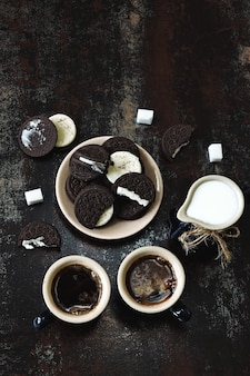 Due tazze di caffè espresso, una caraffa di latte e biscotti al cioccolato con ripieno bianco.