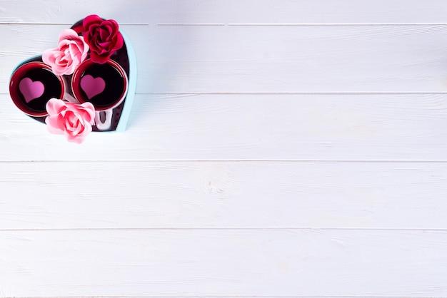 Due tazze di caffè in una scatola di un cuore su uno sfondo bianco. san valentino