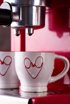 Due tazze di caffè nero mattina sulla macchina per il caffè rosso.
